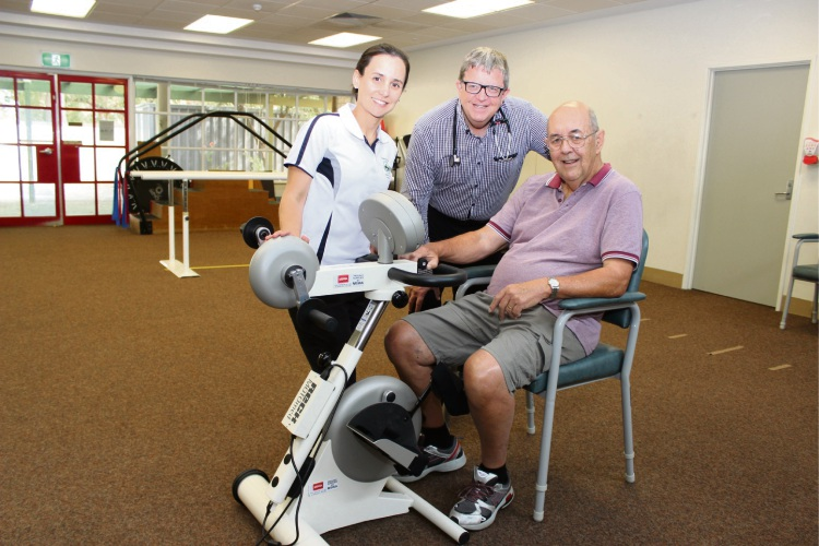 Osborne Park Hospital senior physiotherapist Tanya Pember, clinic head of services Barry Vieira and patient Kent Piercy with the donated motorised therapy bike.