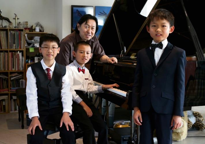 Jing Quan Chong (10), Tian Liang (8) and Vincent Zhu (10) with piano teacher Yoon Sen Lee. Picture: Matt Jelonek.
