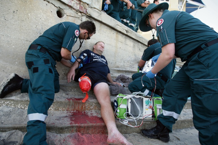 Student ambulance officers Rod Fellows (left) and Jesse George attend fake shark attack victim Phil Van de Naport. Picture: Bruce Hunt