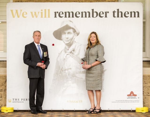 RSLWA chief executive John McCourt and Perth Mint group manager Alison Puchy place the first poppies on The Perth Mint centenary poppy wall of remembrance.