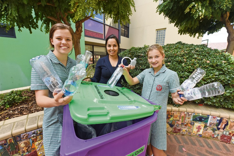 Year 9 Jade Destremau, chemistry teacher and Eco Sisters co-ordinator Hannah Fay and Year 7 Tessa Pickett with the purple bins used to collect plastic bottles.