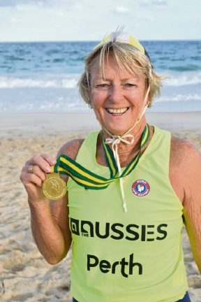 Kay Smith proudly displays her gold medal for her beach run. Picture: Max Wannell
