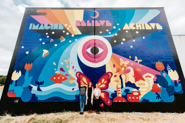 Kolbe College students Elyssa Bennett, Isabella Manolas, Taya Ball with mural on the Sterling Office National building.