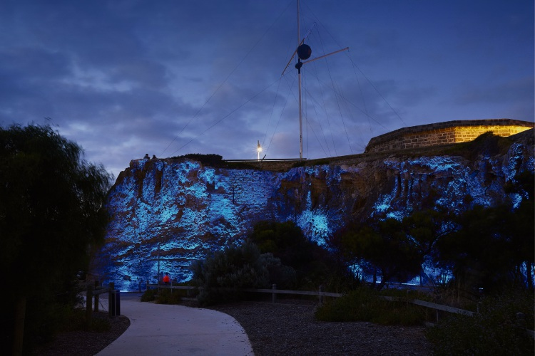 The cliffs next to the Round House illuminated blue.