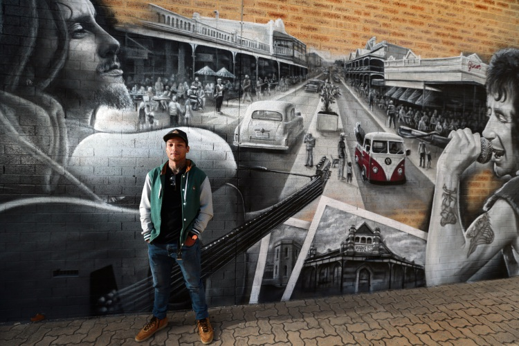 Street artist Joseph Boin (South Fremantle) with his mural at the Federal Hotel. Photo: Martin Kennealey