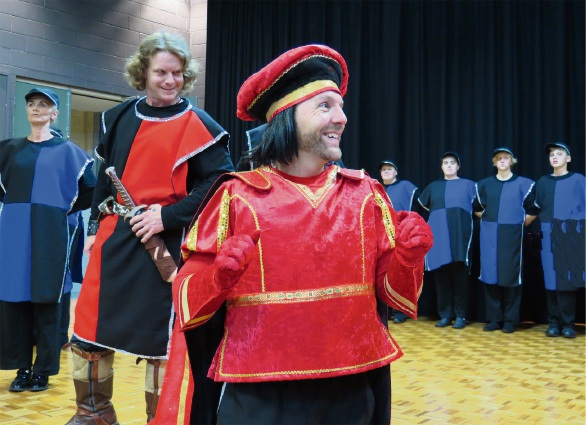 The diminutive Lord Farquaad (Paul Hayward) surveys his subjects, watched by the Captain of the Guard (Leigh Hunter).