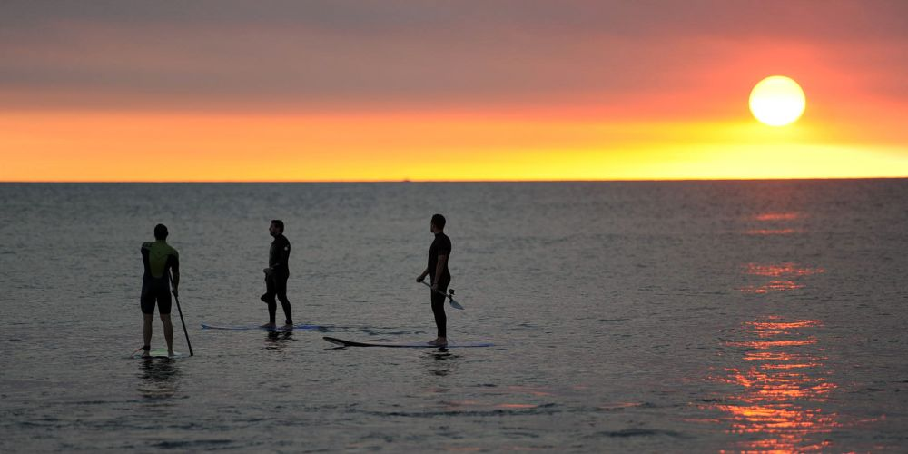 A Blood setting sun captured stand-up paddlers at Telephone Box. Pictures: Jon Bassett