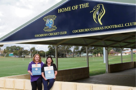 SMHS health promotion officer Ruth Aspinall and Gloria Askander from the City of Cockburn with the new smoke-free sign at the Cockburn Cricket Club.