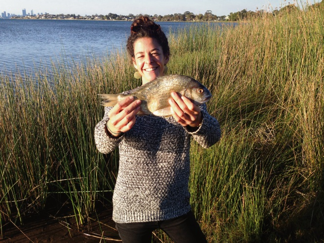 Murdoch University PhD researcher Clara Obregn holding a black bream on the banks of the Swan River in Perth.