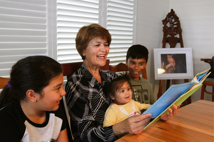 Nanette Esam reading Bumpel Swivet to grandchildren Emily, Lachlan and baby Ivy Ford, with a photograph of daughter Rebecca Anderson in the room. Photo: supplied