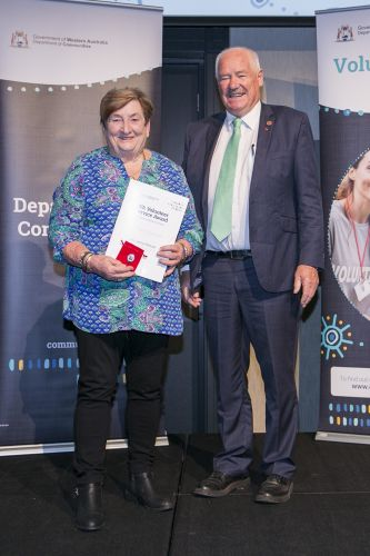Volunteering Minister Mick Murray presents Jenny Rosser with her award.