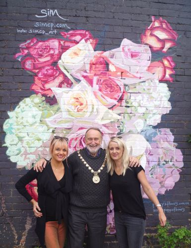 Artist Sim Campbell-Pope, Nedlands mayor Max Hipkins and Poppy's owner Milly Dempster in front of the new mural.
