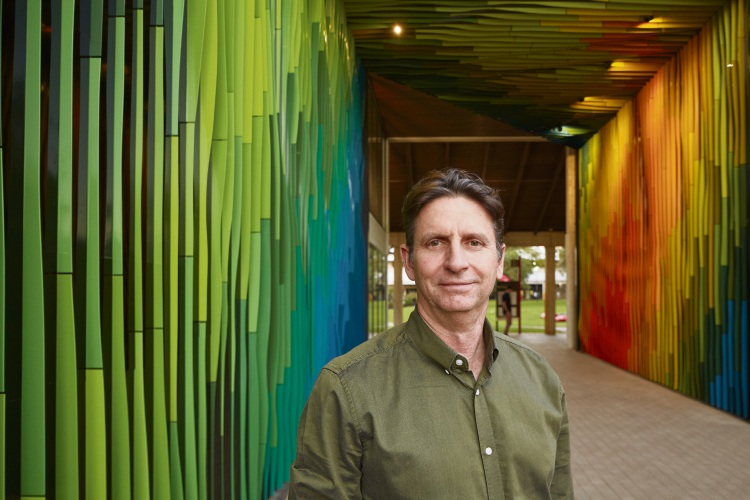 Stuart Green stands next to his colourful artwork, which climbs up the walls and the roof.