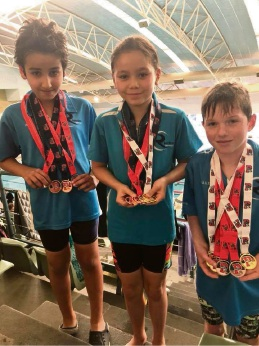 Ali Al Naser (8), Mackenzie Bell (10) and Bailey Minderman (9) with their medals.