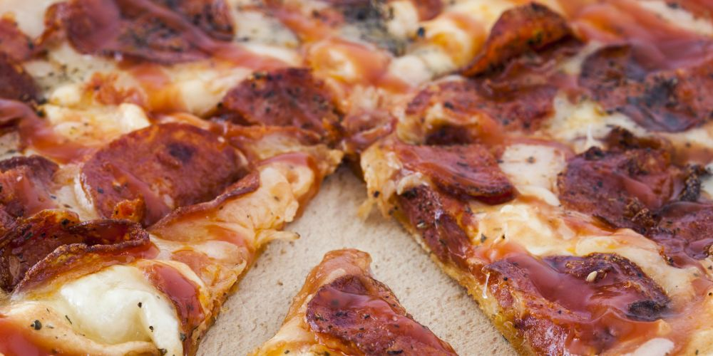 A closeup on a sliced pepperoni pizza pie.