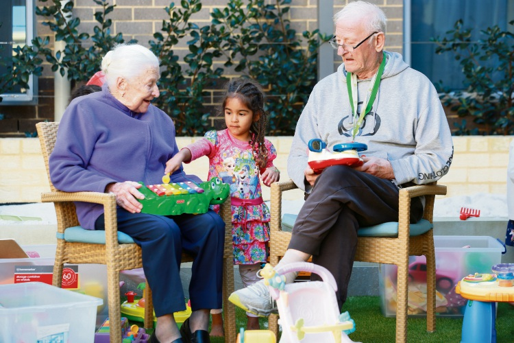 Sophia Barber with 4 year old Amelia Perera and John Hawke. Kids and elderly people interacting as part of the intergenerational playgroup at Bethanie Gwelup aged care facility. Photo: Andrew Ritchie