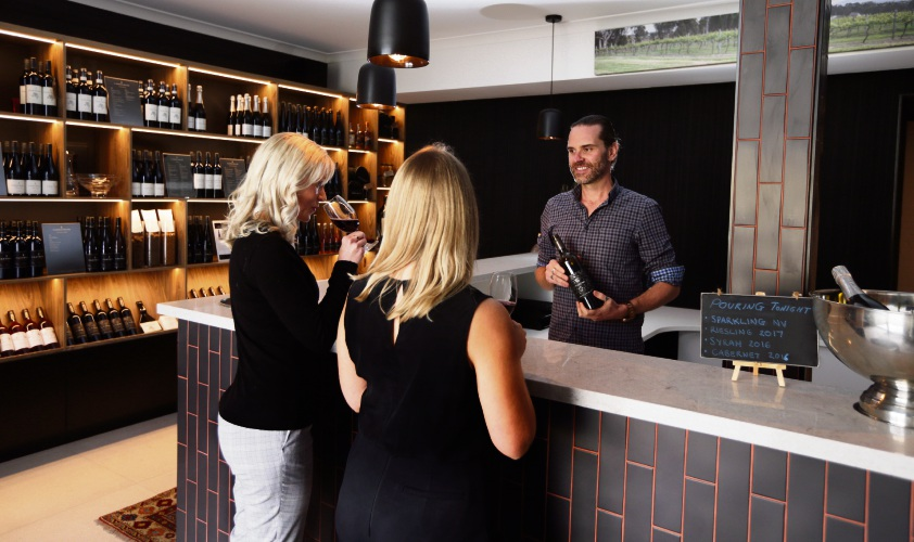 Castelli Estate Wines brand manager James Majer pours wine for Joanne Bennier and Alyce Thompson. Picture: Martin Kennealey.