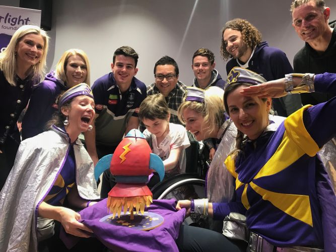 Sahara Pittaway, Captain Starlights, Starlight chief executive Louise Baxter, and ambassadors Mike Hussey, Herb Faust and Fremantle Dockers players cutting the cake at the new Starlight Express Room. Picture: Jessica Warriner.