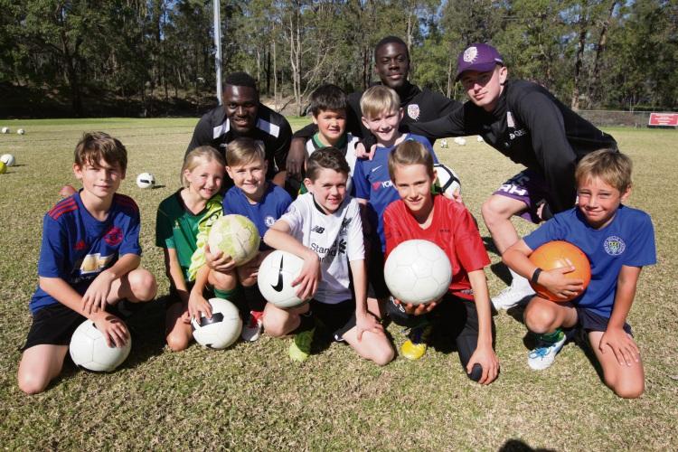 Glory soccer coaches Abduh Dulleh, Michael Domfeh & Callum Dobbs with local kids. Photo: Bruce Hunt