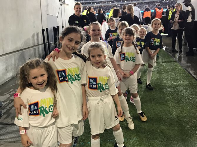 The ten girls from Queens Park Soccer Club in the Optus Stadium player tunnel after their experience.