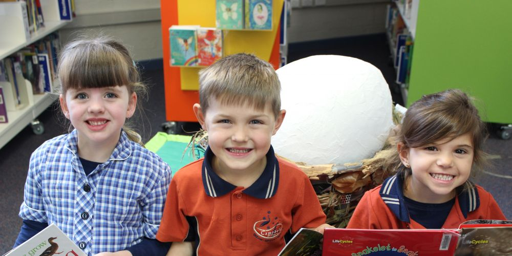 Campbell Primary School's Molly Boxall,  Jean Du Plessis and Luciana Healy-Soler enjoy a book as part of the Paint the Highway REaD campaign.