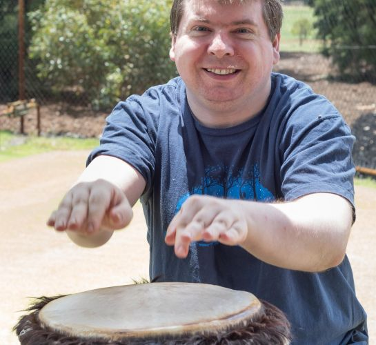 Crosslinks participant Paul Wilson getting great enjoyment from using a drum outdoors.