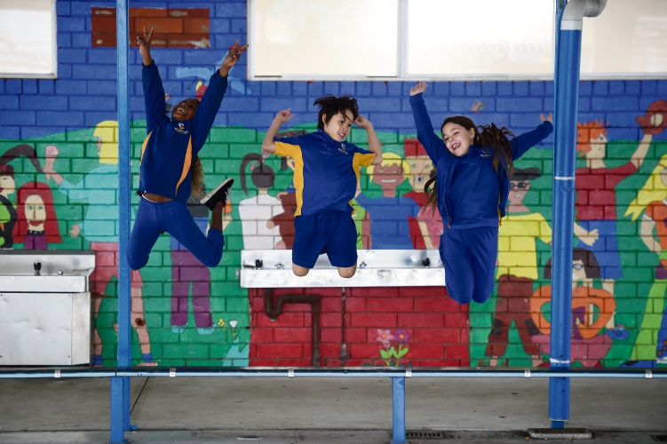 Brookman Primary School students Neria Niciteretse (Yr4), Nero To (Yr3) & Khodi Vergeer (yr3). jump for joy that their school has been recognised