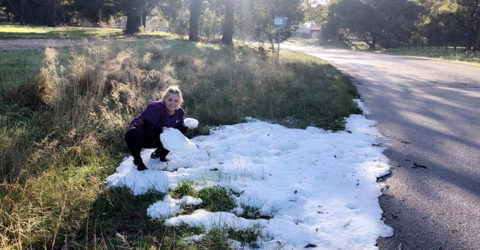 Dawesville resident Charlene McCall with a mountain of hail on the edge of a road in Pleasant Grove Circle.