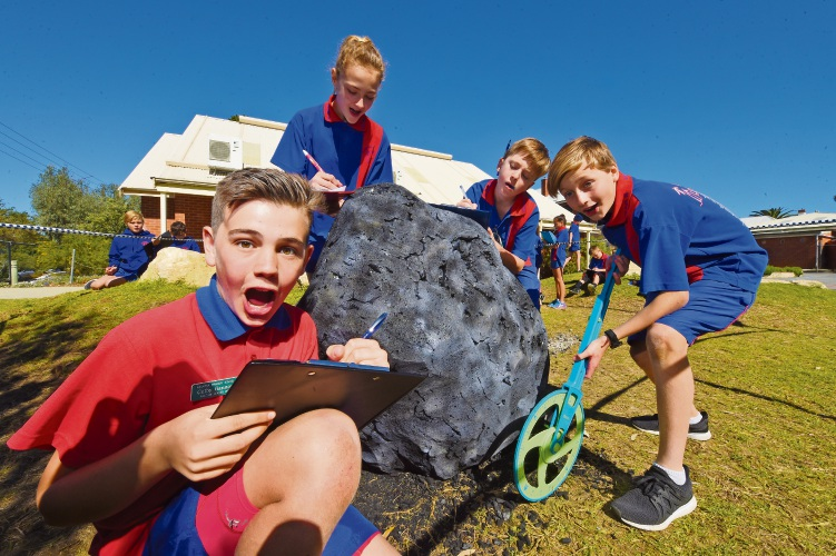 Palmyra Primary School Year 6 students Colby Gannon, Ellie Nichols, Lachlan Godfrey and Riley Heppekausen investigate the meteorite. Picture: Jon Hewson.
