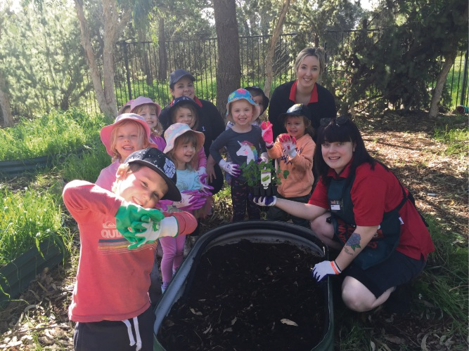 Kindy room leader Sian Davies, director Shanice Drew and Bunnings activity organiser Jamie-Lee Plenderleith with children at the planting.