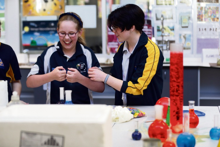 Hocking Primary School Year 6 student Marcail Mounder and Wanneroo Secondary College Year 10 student Morgan Sampson take their turn at the various activities on offer during Wanneroo Secondary's innovation fair. Pictures: Martin Kennealey d485511 www.communitypix.com.au