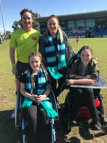 Hayley (12) and Jaimie (14) Topham with their mother Narelle and a WAFL umpire.