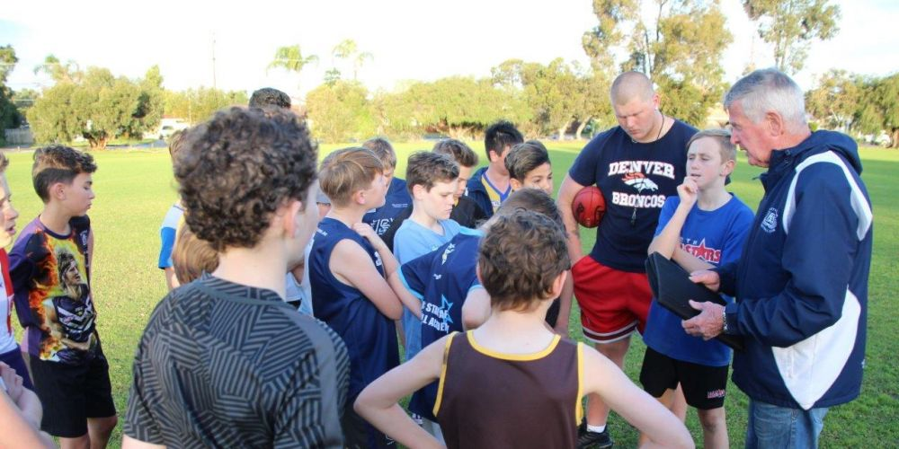 John Greenwood (far right) talking to his Willetton Junior Football Club's Under 12's side.
