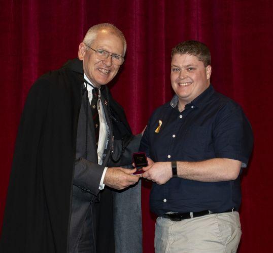 St John chief executive Tony Ahern presents Mark Hampshaw with his award.