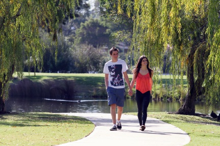 Michael Woods and Tia Ucich enjoy a walk beneath shady trees at Berrigan Lake in South Lake.