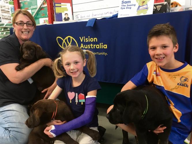 Seeing eye dog instructor crouching Kay Whitely holding Sky, Annaliese Verkuylen holding Arthur, and Leon Verkuylen holding Lucy.