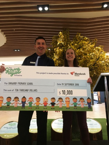 Oakwood Primary School principal William Davis and centre manager Jacqueline McKenzie with the $10,000 cheque.