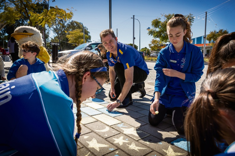 Adam Selwood and student leaders from Lathlain Primary School kickstart the colouring process outside Lathlain cafe Laika. Picture: Will Russell.