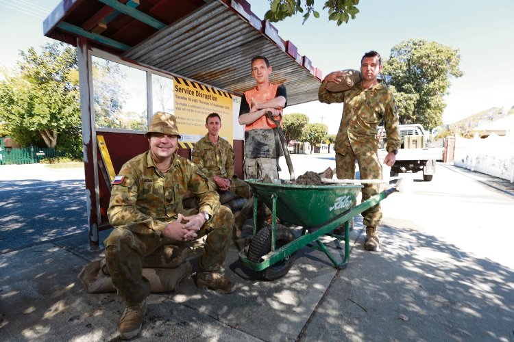 Australian and New Zealand soldiers sandbag the bus stops. Picture: Andrew Ritchie.