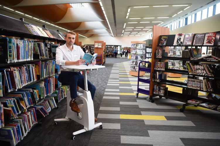 Library officer Oliver Black on one of the reading bicycles at AH Bracks Library. Picture: Jon Hewson