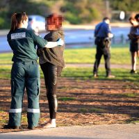A paramedic consoles the victim while police interview a witness. Picture: Jon Bassett.