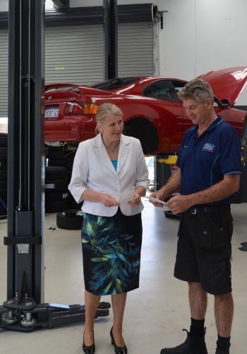 Mayor Carol Adams with Mark Fletcher of B&M Automotive in Calista alongside the new car hoist, partially funded with a Activity Centre Improvement Grant from the City in 2017, that will support the expansion of his business.