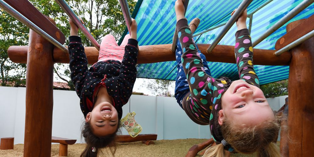 Annette Tjing and Nina Young play on the monkey bars at Goodstart Early Learning Alfred Cove's new nature playground. Picture: Jon Hewson