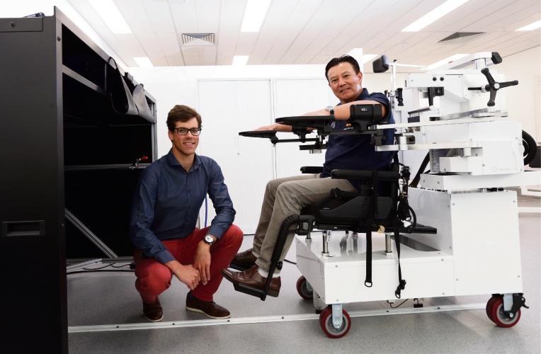 Research fellow Dr Onno van der Groen and Professor Ken Nosaka with the KinArm robot. Pictures: Martin Kennealey d486941
