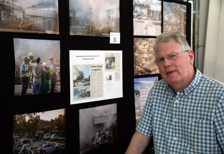 Richard Goodwin with some of the images he captured when fire tore through The Downs Shopping Centre. Photo: Martin Kennealey