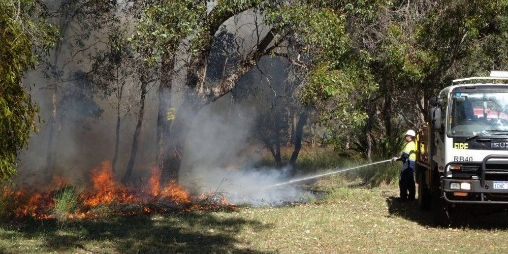 An officer hoses down a controlled burn at Scenic Drive, Wanneroo. Picture: Gary Tate