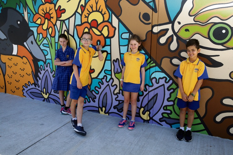 Olivia, Nate, Taryn and Jack with the mural painted for Bambara Primary School's anniversary. Picture: Martin Kennealey.