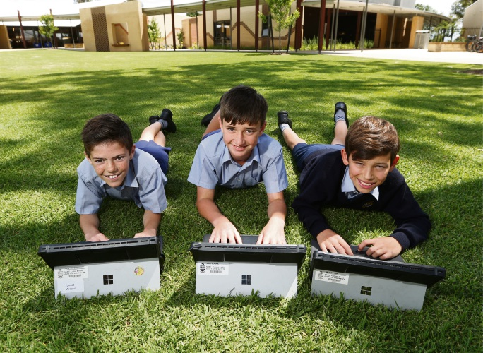 Y6 Hale school students Lucas Arnold, Thomas Carter and Zach Grant getting some fresh air as they do their school work on the new junior school campus. Photos: Andrew Ritchie