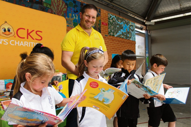 Dymocks Children's Charities General Manager Paul Swain and Kewdale Primary School Year 1 students with their new books.