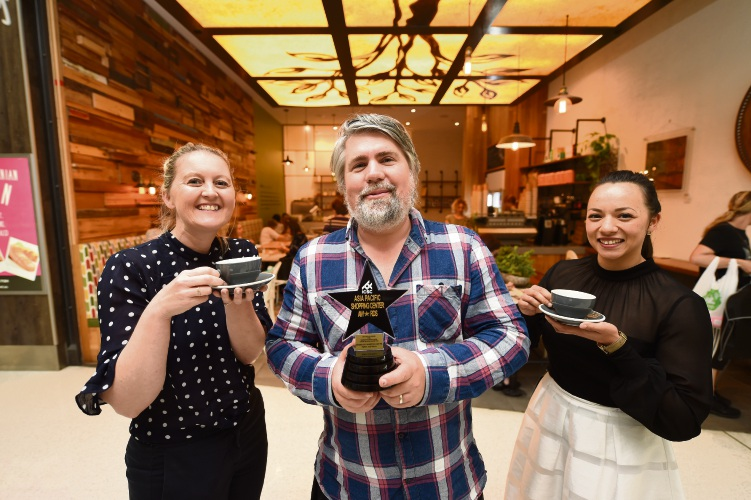 Coffea owner Euro Lumb, centre, carries the award, with Garden City Shopping Centre senior marketing manager Clare Riley and brand and communications officer Giselle Posilero. Picture: Jon Hewson